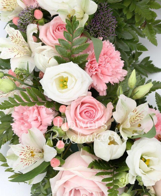 10 trandafiri roz, 15 garoafe roz, 5 alstroemeria alba, 10 lisianthus alb, 10 hypericum roz, 10 lalele albe, 10 trachelium mov, ferigă, waxflower, suport colac