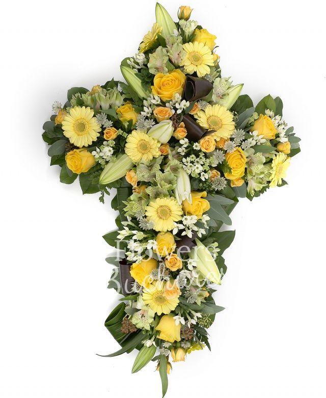 10 bouvardia alba, 5 crini, 10 trandafiri galbeni, 10 miniroze galbene, 5 astranția alba, 10 gerbera galbenă, 5 alstroemeria galbenă, eucalypt, ferigă, salal, aspidistra, suport cruce