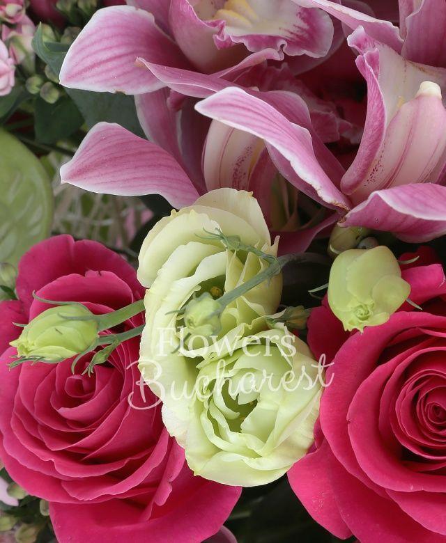 5 trandafiri cyclam, 4 lisianthus roz, 3 santini roz, 5 garoafe crem, 2 lisianthus verde, 2 sedum, 4 bouvardia roz, 2 anthurium verde, cymbidium roz, eucalypt, salal, cuib